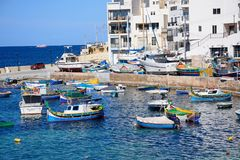 Boats in San Pawl harbour, Malta. Traditional Maltese Dghajsa fishing boats moored in the harbour with town buildings to the rear, San Pawl, Malta, Europe Stock Photos