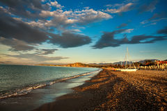 Boats on sandy sea beach in dawn sky background Stock Photos