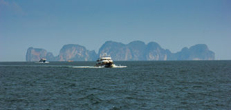 Boats at sea against the rocks in Thailand Stock Photo