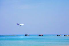 Boats in sea and airplane on blue sky Royalty Free Stock Photography