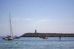 Boats on the sea and pier with red lighthouse stock photo