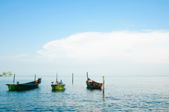 Boats by the sea shore. Some shallow water fishing boats tied-up at some poles by the sea shore Stock Photo