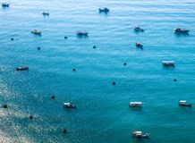 Small and large boats in the sea. Small and large boats of Vietnamese sailors in the blue sea. The left corner is the reflection of the sun on the water stock image