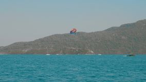 Boats on sea waves and person parasailing above water. Scenic view of beautiful sea harbour with vessels and person gliding through air wearing open parachute stock video footage