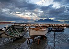 Boats on seacoast in Naples. Boats on the seacoast in Naples and Mount Vesuvius in the background, Italy royalty free stock photos