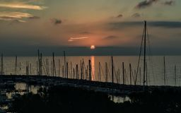 The boats in shadow and a peaceful sunset in Trieste royalty free stock photo