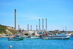 Delimara Power station and harbour, Marsaxlokk. Boats and ships in the harbour with Delimara power station to the rear, Marsaxlokk, Malta, Europe Stock Photo