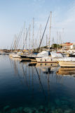 Boats and ships at pier in Rovinj, Croatia at sunset. Masts are reflected in the sea. Stock Image