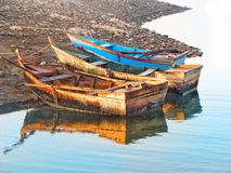 Boats on a shore. Boats on a lake shore, tied by ropes. Reflection is visible in water Royalty Free Stock Photography