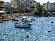 Boats and a small beach on the embankment of the tourist town of Loutraki stock photos