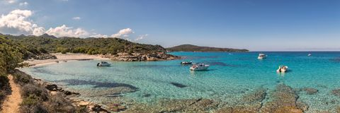 Boats in a small rocky cove with sandy beach in Corsica Stock Image