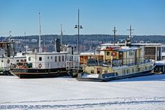 Frozen harbour in Lahti, Finland. Boats at snow covered frozen harbour in Lahti, Finland at sunny winter day Royalty Free Stock Photos