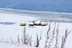 Boats on snow-covered shore. Boats on snow-covered bank of river Royalty Free Stock Images