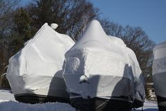 Boats with Snow and Shrink Wrap. Plastic shrink wrap on boats, to protect boats and interior of boats from the winter elements Royalty Free Stock Photography