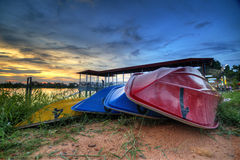 Boats stack at the river bank with sunset background. The boat was colourful and has number on its body Royalty Free Stock Image