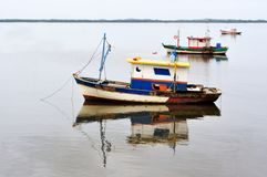 Boats in still water. Three fishing boats anchored in still water waiting for their owners to sail in another fishing journey Royalty Free Stock Photography