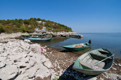 Boats on the stone beach. Of the Skadar lake in Montenegro Royalty Free Stock Photo