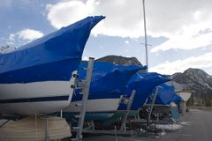 Boats in storage 1. A line of boat bows on boats stored in the Colorado mountains, covered in shrinkwrap blue plastic, wait for summer sailing season Stock Photo