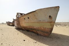 Rusty boats of the Aral Sea. Boats stranded on the now dry bottom of the Aral Sea. The sea has dried up, leaving only sand, seashells, rusty boats and unique and Stock Photography