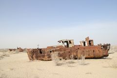 Rusty boats of the Aral Sea. Boats stranded on the now dry bottom of the Aral Sea. The sea has dried up, leaving only sand, seashells, rusty boats and unique and Stock Photo