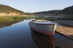 Boats in the summer evening at a wooden pier on the Sukhona River in the tract of Opoki. Opoki, Velikoustyugsky district, Vologda region, Russia - August 12 Stock Photos