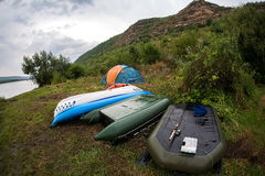 Boats and a tent on the banks of the river. Stock Photography