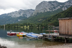 Boats tied to old pier, lake Toplitzsee, Austria Stock Photos