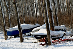 Boats to winter. Boats wintering in the poplar forest on the shores of the river. Snow is a warm coat for boats royalty free stock photos