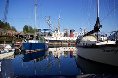 Boats in Tofino, British Columbia, Canada, reflected in harbour waters Stock Image
