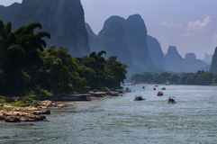 Boats with tourists cruising in the Li River with the tall limestone peaks in the background near Yangshuo in China Royalty Free Stock Photos