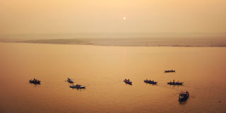 Boats with tourists at Ganga river - vintage filter. Sunrise in Varanasi. Stock Photos