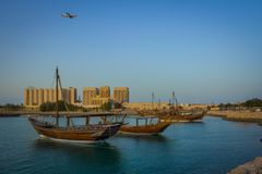 Boats traditional dhow in Arabic gulf. With plane in the sky Stock Images