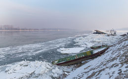 Boats trapped on the bank of the frozen river Royalty Free Stock Photography