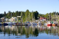 Boats and trees in Tofino, Canada, reflected in harbour waters Royalty Free Stock Photo