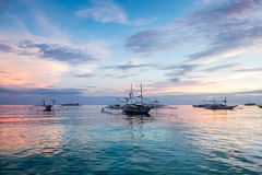 Boats on a tropical beach at sunrise royalty free stock photography