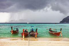 Boats in the tropical sea under gloomy dramatic sky Royalty Free Stock Photo