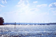 Boats on tropical sunlit silver sea. A photograph showing a row of many little sail boats lined up against the horizon on a hot sunny summer afternoon under a royalty free stock images