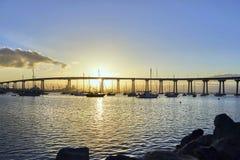 Boats under and beautiful sunrise over the Coronado Bridge, San Diego California. Always perfect weather and perfect sunrises in sunny San Diego, California royalty free stock photo