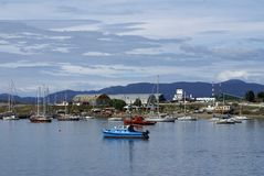 Boats in Ushuaia Harbor with the airport in the background. Boats moored in Ushuaia Harbor, Argentina, with the airport in the background Royalty Free Stock Photos