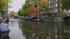 Boats, vessel, bicycles along Amstel canal, Amsterdam, Netherlands Royalty Free Stock Images