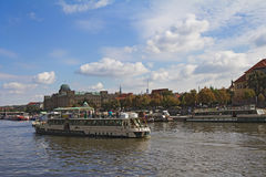 Boats on Vltava river with historical buildings in background Royalty Free Stock Photo