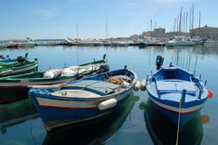 Boats waiting to sail. Moored boats inside the little harbor in Syracuse. Typical sicilian fishing boats Royalty Free Stock Image