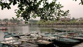 The boats are waiting for tourists. Anchored and lined up on the green river which looks very beautiful, the far side is coconut trees and small lovely houses stock images