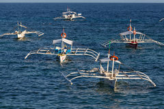 Boats waiting for tourists in sea water to travel between the islands. Island Panglao, Philippines Stock Images