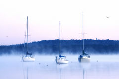 Boats in water on cold foggy morning Stock Photos