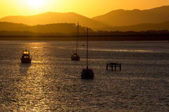 Boats on water with sunset behind. Boats in silhouette with sunset and mountains behind Stock Photo