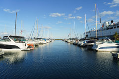 Boats. Waterfront marina with boats and a clear sparse cloudy sky. Bright light. Perspective view along the center of the image Stock Images