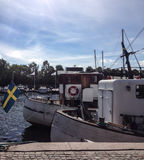 Boats on waterfront. Of Swedish city with national flag. Summer season Royalty Free Stock Photo