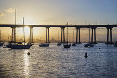 Boats and waves glistening at sunrise under the Coronado Bay Bridge in San Diego, California. Shot in the early morning hours from Coronado Island across the bay royalty free stock photo