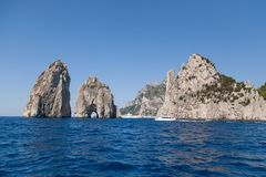 Faraglioni, the natural arches of Capri, Italy. Boats in wavy blue water in front of the natural arch formations, or Faraglioni, in the Bay of Naples in Capri Stock Photos